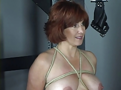 Bare redhead with  jugs and backside is flagellated in domination & submission dungeon space
